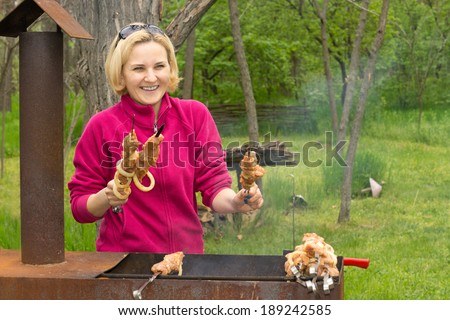 Happy attractive blond woman cooking on a BBQ standing smiling at the camera with her hands full of prepared uncooked kebabs which she is placing on the grill over the fire to cook - stock photo
