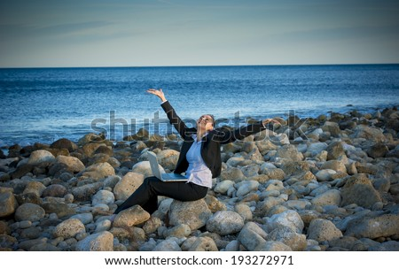 happy attractive business woman wearing suit working on computer sitting on some rocks at the beach looking up to sky thinking about freedom - stock photo