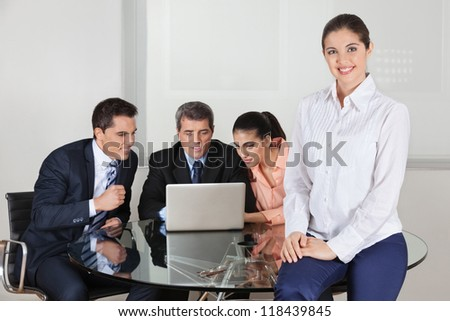 Happy attractive business woman with her team around a laptop in the office - stock photo