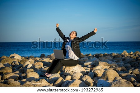 happy attractive business woman working on a laptop sitting in front of the sea on some rocks at the beach looking up to blue sky with opened arms thinking about freedom - stock photo