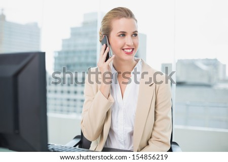 Happy attractive businesswoman on the phone in bright office - stock photo