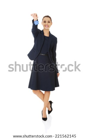 Happy attractive businesswoman, real estate agent, holding a house key - stock photo