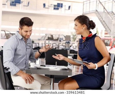 Happy attractive caucasian businesswoman representative with male client at car saloon reviewing business papers. Sitting at coffee table, gesturing. Smiling, wearing dress. - stock photo