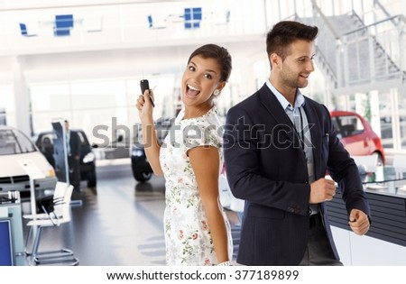 Happy attractive caucasian lady with new car keys at dealership indoors. Standing smiling looking at camera in car saloon with business sales representative.