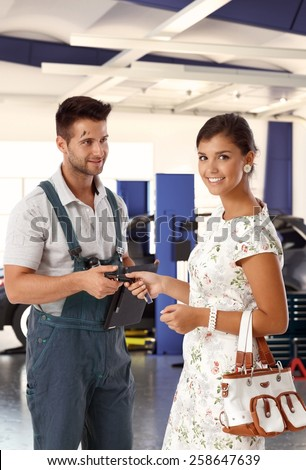 Happy attractive caucasian young woman at auto repair business shop, giving car keys to handsome dirty male mechanic. Smiling standing looking at camera. - stock photo