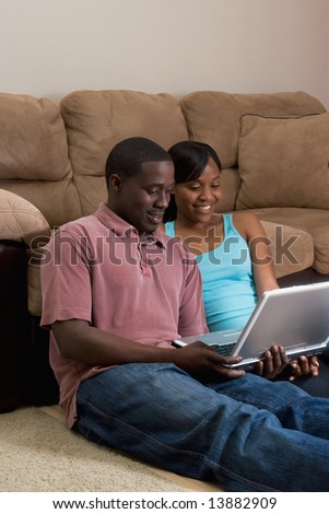 Happy, attractive, couple sitting on the floor in front of a couch. They are looking at  a laptop computer together. She has her arm on his shoulder. Vertically framed photograph