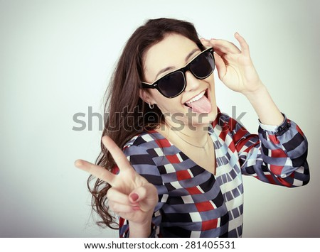 Happy attractive excited teen girl shows tongue, toned - stock photo