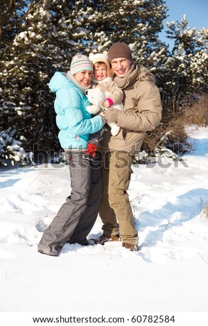 Happy attractive family in a snowy park - stock photo