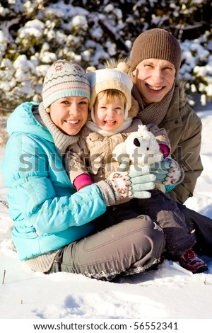 Happy attractive family playing in snow - stock photo