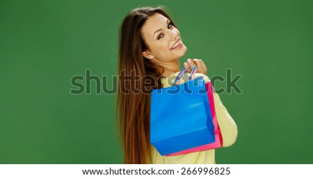 Happy attractive female shopper carrying her purchases in brightly colored carrier bags turning to smile over her shoulder at the camera - stock photo