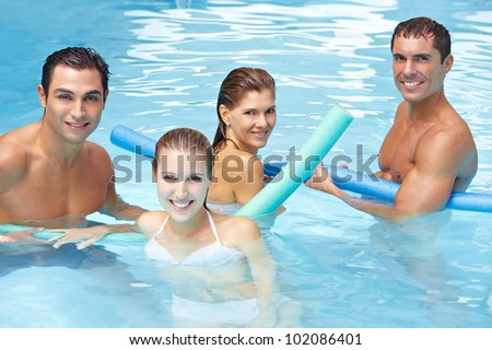 Happy attractive friends bathing with swim noodles in swimming pool - stock photo