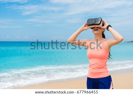 happy attractive girl jogger wearing VR technology glasses standing on beach and adjusting device to viewing 3D simulation video.