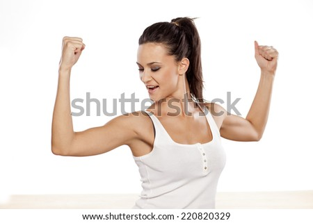 Happy attractive girl showing her biceps - stock photo