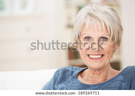 Happy attractive grey-haired senior woman with a beautiful smile relaxing at home on a sofa looking at the camera with copyspace alongside