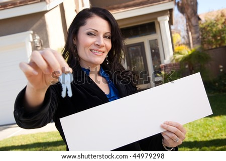Happy Attractive Hispanic Woman Holding Blank Sign and Keys in Front of House. - stock photo