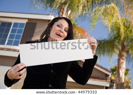 Happy Attractive Hispanic Woman Holding Blank Sign in Front of House. - stock photo