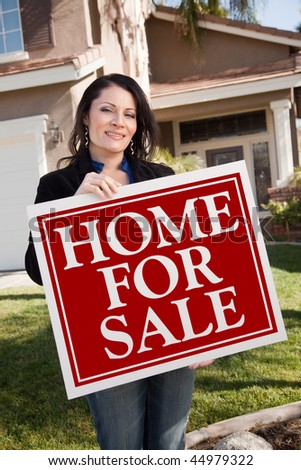 Happy Attractive Hispanic Woman Holding Home For Sale Real Estate Sign In Front of House. - stock photo
