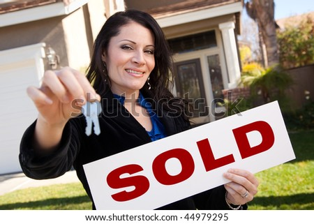 Happy Attractive Hispanic Woman Holding Keys and Sold Sign In Front of House. - stock photo