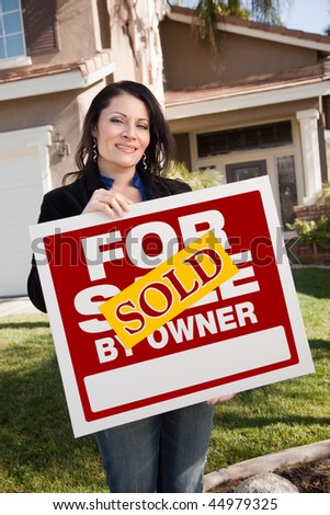 Happy Attractive Hispanic Woman Holding Sold For Sale By Owner Real Estate Sign In Front of House - stock photo