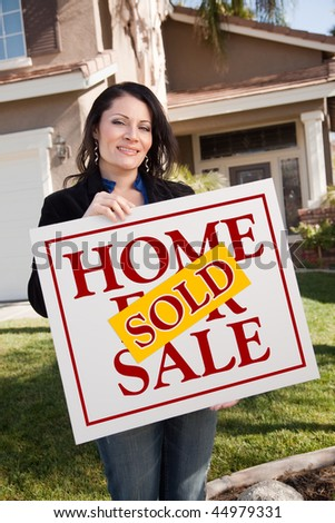 Happy Attractive Hispanic Woman Holding Sold Home For Sale Sign In Front of House.