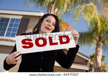 Happy Attractive Hispanic Woman Holding Sold Sign In Front of House. - stock photo