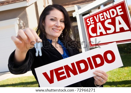Happy Attractive Hispanic Woman Holding Vendido Real Estate Sign and Keys in Front Se Vende Casa Real Estate Sign and House.