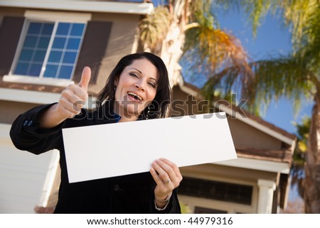 Happy Attractive Hispanic Woman with Thumbs Up Holding Blank Sign in Front of House. - stock photo