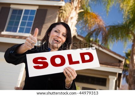 Happy Attractive Hispanic Woman with Thumbs Up Holding Sold Sign In Front of House. - stock photo