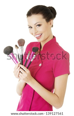 Happy attractive make-up artist woman holding brushes - stock photo