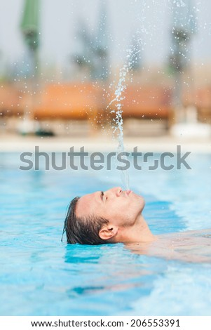 Happy attractive man leaning at edge of swimming pool, relaxing and having fun