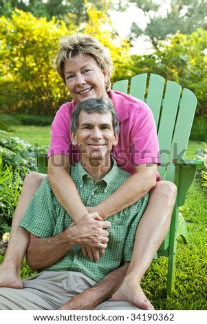 Happy, attractive, mature couple hugging and relaxing outdoors - stock photo