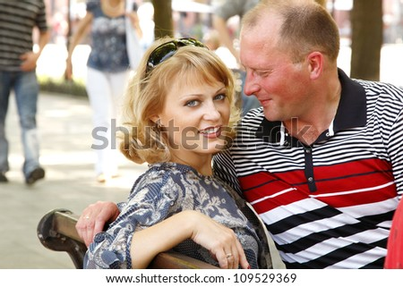 Happy attractive mid adult couple have fun outdoor. Wife and husband in city park