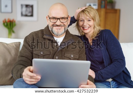 Happy attractive middle-aged couple at home relaxing together on a sofa with a laptop computer smiling at the camera - stock photo