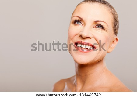 happy attractive middle aged woman looking up and smiling - stock photo