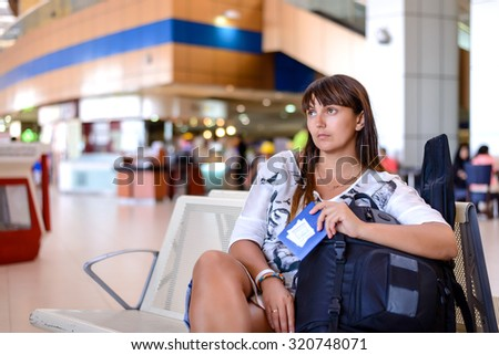 Happy attractive middle-aged woman sitting in an airport lounge with her luggage surrounded by a crowd of passengers as she waits for her flight