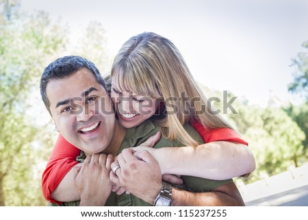 Happy Attractive Mixed Race Couple Piggyback at the Park. - stock photo