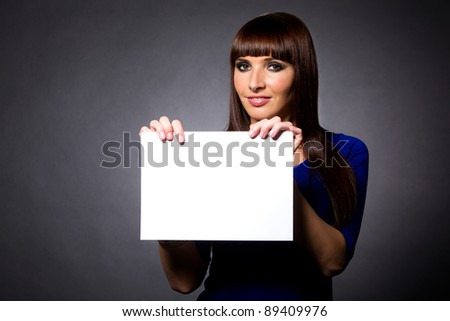 Happy attractive model holding white sign in studio