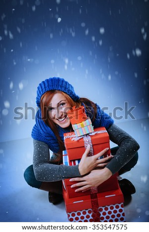 Happy attractive redhead woman sitting cross-legged on the ground clasping a pile of colorful red Christmas gift boxes under falling winter snow with copy space for your seasonal holiday greeting