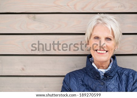 Happy attractive senior lady standing against a wooden clad building smiling at the camera with copyspace alongside - stock photo