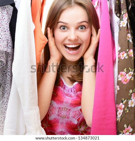 Happy attractive teen girl among clothes in wardrobe or in shop - stock photo