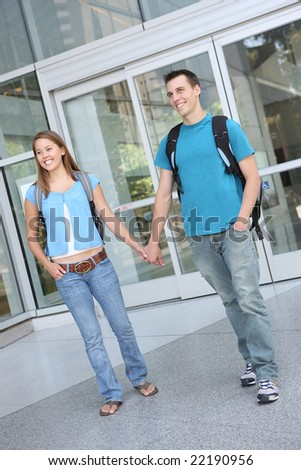 Happy attractive teenage couple at school library