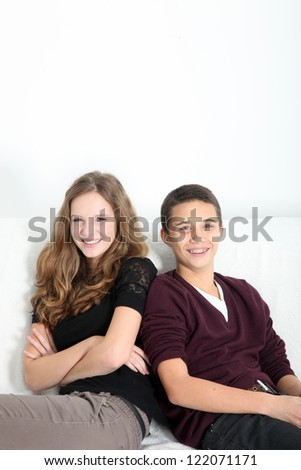 Happy attractive teenage couple sitting together on a couch with overhead copyspace smiling charmingly at the camera - stock photo