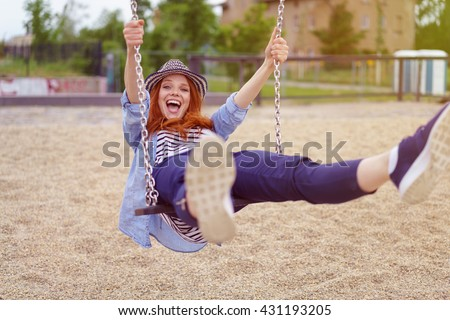 Happy attractive trendy young woman laughing as she plays on a swing on a sandy beach or urban park - stock photo