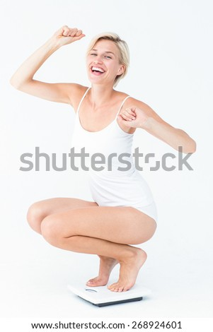 Happy attractive woman crouching on a scales on white background - stock photo