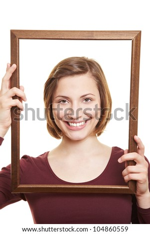 Happy attractive woman in empty wooden picture frame - stock photo