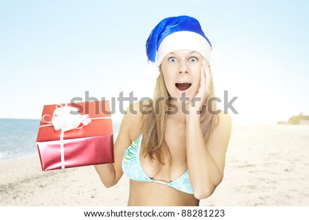 happy attractive woman in santa hat holding christmas gift at the beach - stock photo