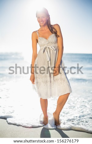 Happy attractive woman in summer dress posing on the beach at dusk