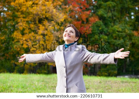 happy attractive woman 50 years in the autumn park - stock photo