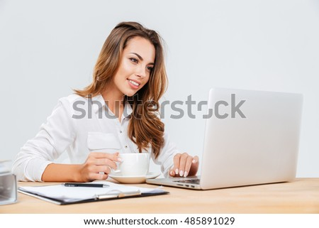 Happy attractive young businesswoman drinking coffee and using laptop over white background