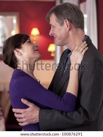 Happy attractive young couple dancing and looking in to each others eyes with tenderness - stock photo